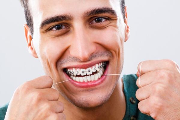 как чистить брекеты зубной нитью
